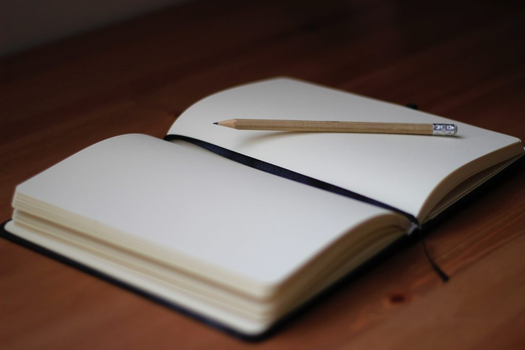 Open notebook with a pencil on it