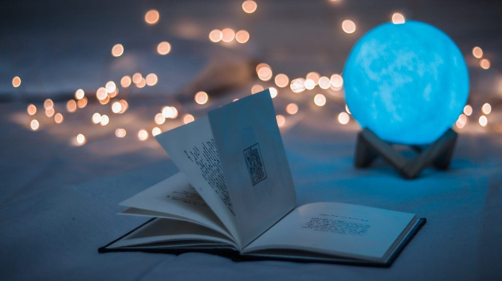 open book and glowing orb sitting on a table